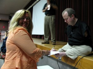 Chet McDoniel signs a book with his feet at an in-service program in Shirley, AR